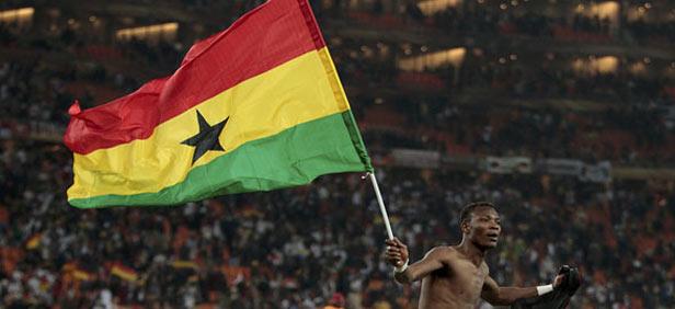 Soccer player holding the flag of Ghana